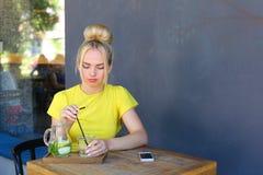 La jeune fille merveilleuse juge le verre disponible, verse la limonade et s'assied Images libres de droits