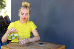 La jeune fille merveilleuse juge le verre disponible, verse la limonade et s'assied Photos libres de droits
