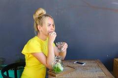 La jeune fille merveilleuse regarde en avant, juge le verre disponible, drinkin Image libre de droits