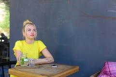 La jeune fille merveilleuse regarde en avant, se repose à la table contre le backgr Image stock