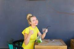 La jeune fille merveilleuse semble en avant et montre des pouces de geste, Image stock