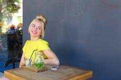 La jeune fille merveilleuse souriant largement, des regards loin, riant, s'assied Photos libres de droits