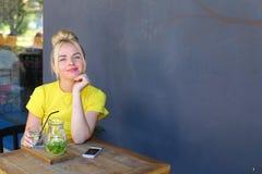 La jeune fille merveilleuse souriant, verre de prises à disposition, des regards à est venue Image stock