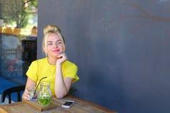 La jeune fille merveilleuse souriant, verre de prises à disposition, des regards à est venue Photo libre de droits