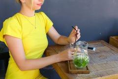La jeune fille merveilleuse souriant, verre de prises à disposition, verse le lemonad Photographie stock libre de droits