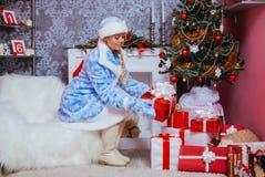 La jeune fille met des présents sous l'arbre de Noël Images stock