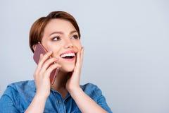 La jeune fille mignonne enthousiaste parle sur son smartphone et sourire images libres de droits