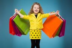 La jeune fille mignonne a habillé tous dans différents sacs de prise jaune photographie stock libre de droits