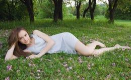 La jeune fille mignonne se penche sur l'herbe verte Image libre de droits