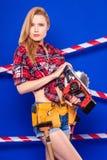 La jeune fille mince de constructeur en rouge chechered la chemise, ceinture de constructeur, je image stock