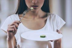 La jeune fille mince mangent le concombre photo libre de droits
