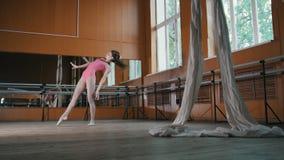 La jeune fille modèle de l'adolescence exécute avec élégance des acrobaties dans la salle de bal banque de vidéos