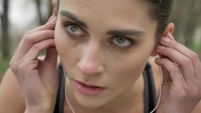 La jeune fille motivée porte des écouteurs et le fonctionnement en parc en été, mode de vie sain, conception de sport clips vidéos