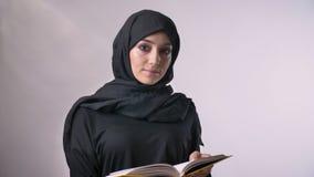 La jeune fille musulmane douce dans le hijab observe à l'appareil-photo et dans le livre, concept religieux, fond gris