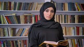 La jeune fille musulmane sérieuse dans le hijab est livre de lecture, observant à l'appareil-photo, le concept religieux, étagère