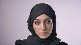 La jeune fille musulmane sérieuse dans le hijab observe à l'appareil-photo, fond gris