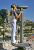 La jeune fille observe la ville avec des jumelles Photographie stock
