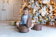 La jeune fille ouvre un cadeau sous un arbre de Noël Photos stock