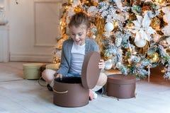 La jeune fille ouvre un cadeau sous un arbre de Noël Image libre de droits