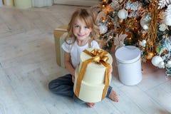 La jeune fille ouvre un cadeau sous un arbre de Noël Images stock