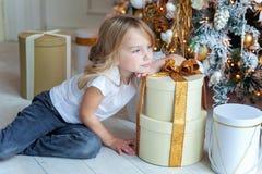 La jeune fille ouvre un cadeau sous un arbre de Noël Photo stock
