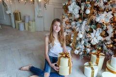La jeune fille ouvre un cadeau sous un arbre de Noël Images libres de droits