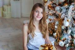 La jeune fille ouvre un cadeau sous un arbre de Noël Photographie stock