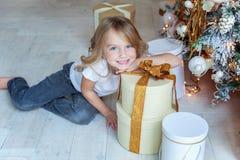 La jeune fille ouvre un cadeau sous un arbre de Noël Photographie stock libre de droits