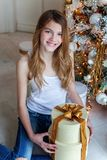 La jeune fille ouvre un cadeau sous un arbre de Noël Photos libres de droits
