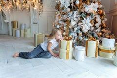 La jeune fille ouvre un cadeau sous un arbre de Noël Photo libre de droits