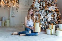 La jeune fille ouvre un cadeau sous un arbre de Noël Image stock