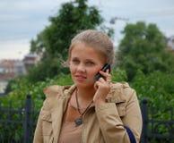 La jeune fille parle au téléphone Photographie stock
