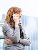 La jeune fille parle par le téléphone portable. affaires photo stock