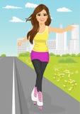 La jeune fille patinant dessus fait du roller sur le trottoir le long de la route Image libre de droits