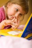 La jeune fille pense avant des ordinateurs portatifs Image libre de droits