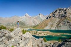 La jeune fille a photographié le lac de montagne Image stock