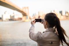 La jeune fille a photographié le pont de Brooklyn Images stock