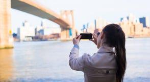 La jeune fille a photographié le pont de Brooklyn Image stock