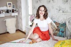 La jeune fille positive sourit dans sa chambre à coucher Photos stock