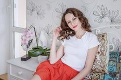 La jeune fille positive sourit dans sa chambre à coucher Image libre de droits