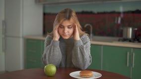 La jeune fille potelée de portrait pense qu'elle devrait manger un hamburger savoureux ou une pomme verte juteuse Choix difficile banque de vidéos