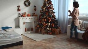 La jeune fille prend l'orange et met le fruit près de l'arbre de Noël banque de vidéos