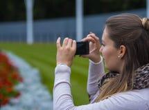 La jeune fille prend une photo à un parc Images stock