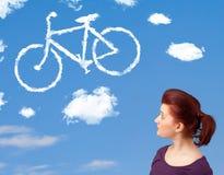 La jeune fille regardant la bicyclette opacifie sur le ciel bleu Photos stock