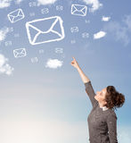 La jeune fille regardant le symbole de courrier opacifie sur le ciel bleu Images stock
