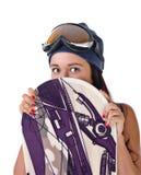 La jeune fille regarde à l'extérieur pour le snowboard Photos stock