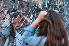 La jeune fille regarde dans un miroir cassé et souffre et se garde par les cheveux Le concept des émotions humaines image libre de droits