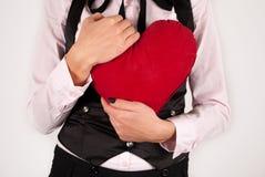 La jeune fille remet à des étreintes le grand oreiller rouge de coeur sur le fond blanc Photographie stock libre de droits