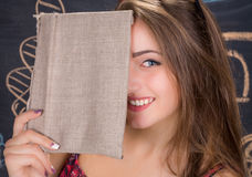La jeune fille riante d'étudiant cache son visage derrière un livre images stock