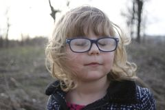 La jeune fille ringarde avec des verres a vieilli 3-5, cheveux blonds, yeux bleus Portraits d'élève du cours préparatoire image stock